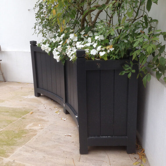 curved planted black painted trough planter